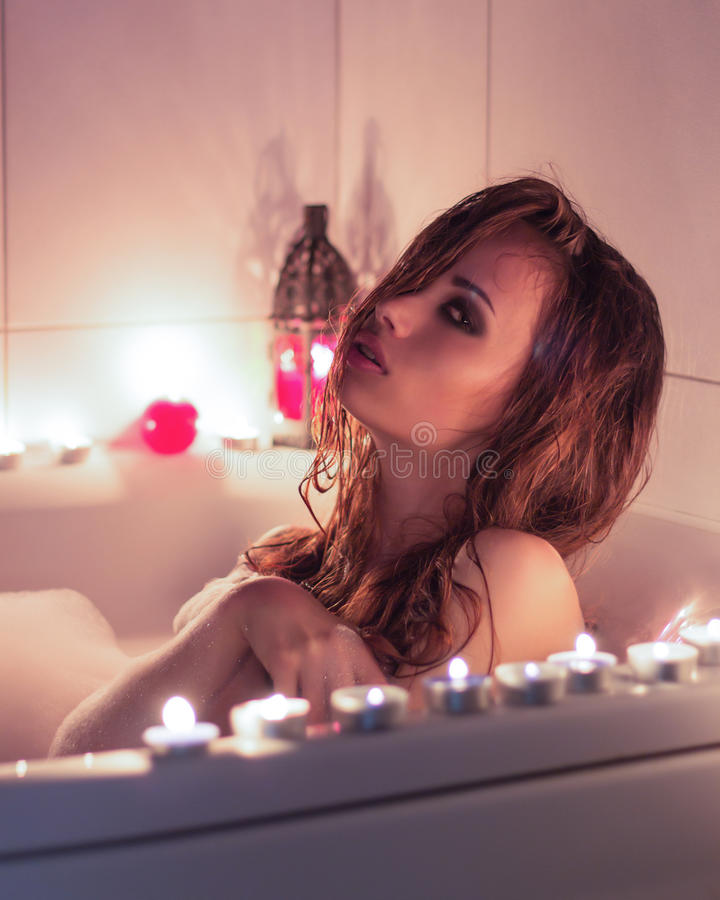 Beautiful young girl with makeup resting in the bath with candles royalty free stock photos