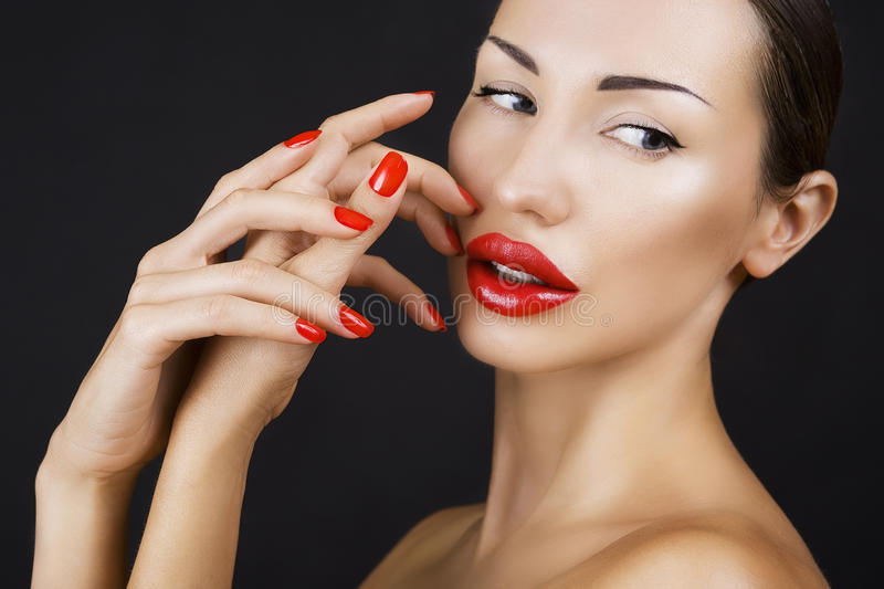 Beautiful Young Girl with Red Lips and Red Nail Polish royalty free stock photography