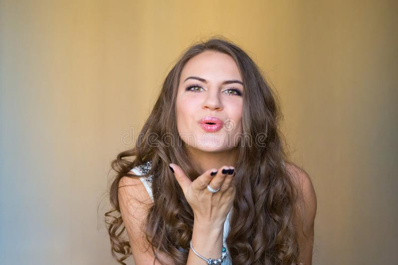 Beautiful and young lady blowing and sending air kiss - nic royalty free stock photography
