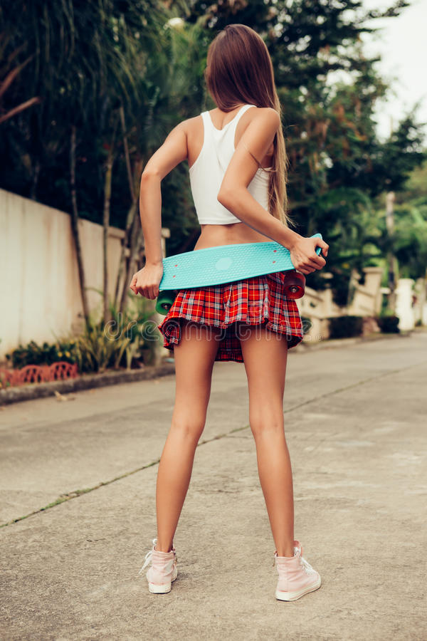 Beautiful young lady in erotic mini skirt with a skateboard. Sporty young lady hold her blue penny skateboard shortboard on a red tartan mini skirt while stands stock images