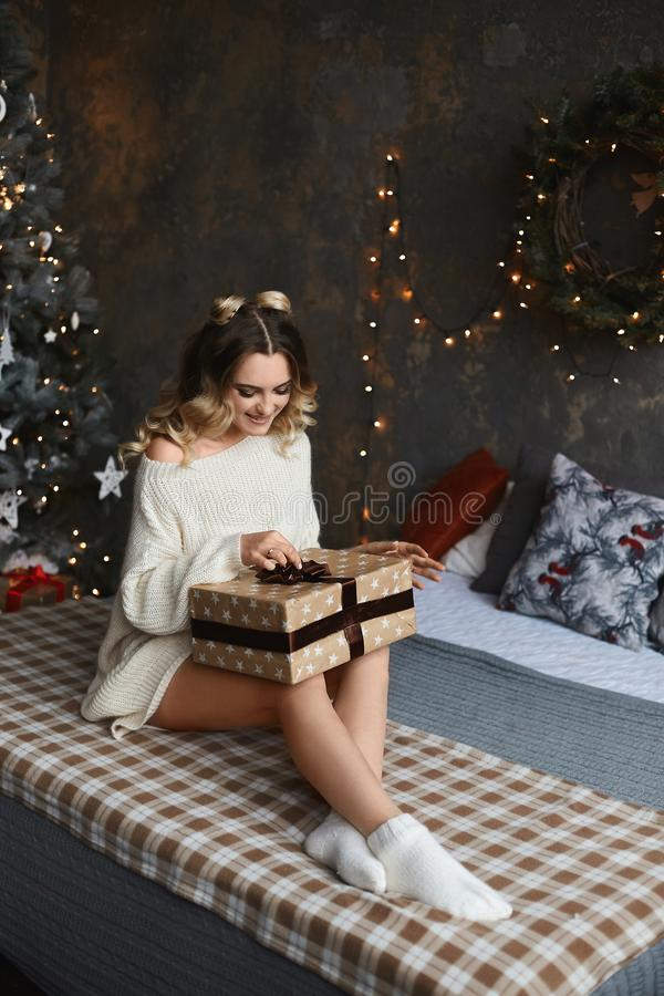 Beautiful and sexy young model woman with sexy legs in oversize sweater sits on the bed, unpacking Christmas gift and. Posing in the interior decorated for New stock images