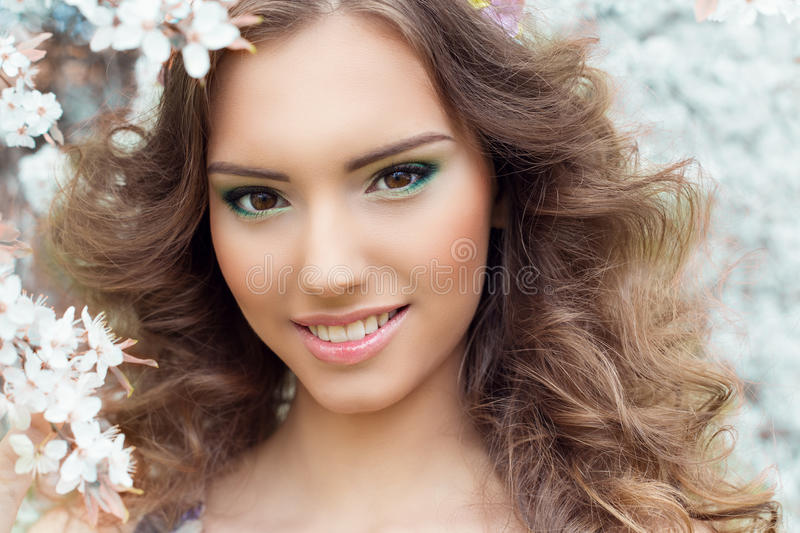 Beautiful young tender sweet smiling girl in a flowered garden with beautiful makeup stock photo