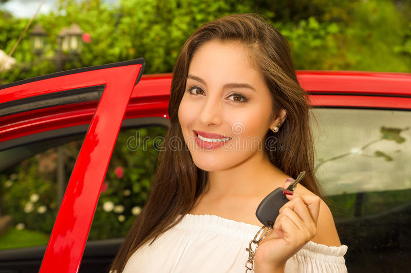 Beautiful young woman holding her keys and smiling and a red car behind.  royalty free stock photography