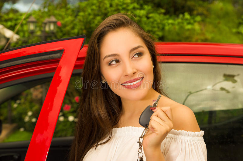 Beautiful young woman holding her keys and smiling and a red car behind.  royalty free stock image