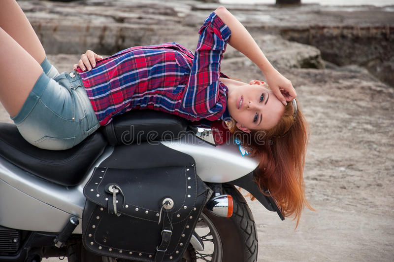Beautiful, sexy, young woman on a motorcycle royalty free stock images