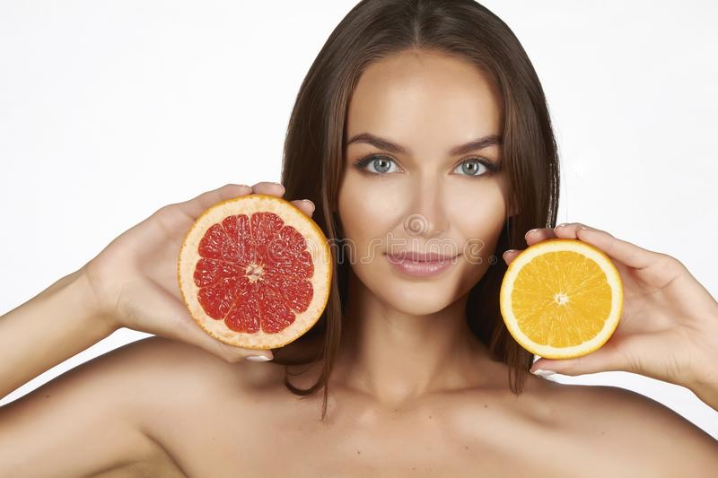 Beautiful young woman with perfect healthy skin and long brown hair day makeup bare shoulders holding orange lemon grapefruit. Healthy eating organic food diet stock photos