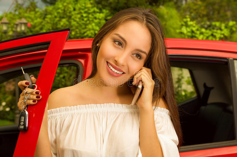 Beautiful young woman in red car holding her keys and using her cellphone while she smiling.  stock photography
