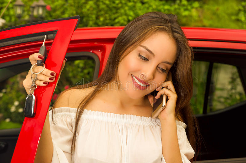 Beautiful young woman in red car holding her keys and using her cellphone while she smiling.  stock images