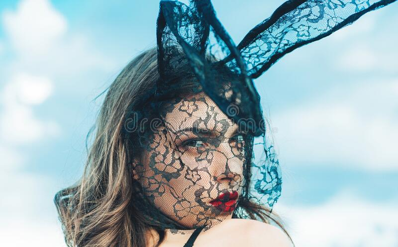 Beautiful sexy young woman wearing a black mask Easter bunny and looks very sensually. Expression face. Nude girl with stock photos