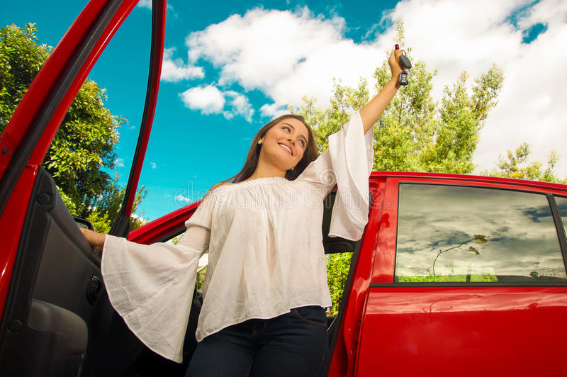 Beautiful young woman wearing a white blouse coming out of her red car and holding a keys while she is smiling.  royalty free stock photo