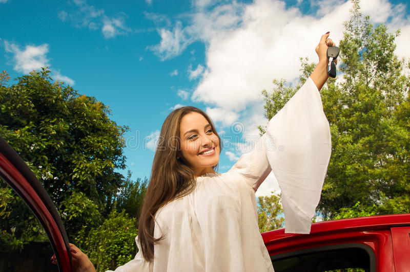 Beautiful young woman wearing a white blouse coming out of her red car and holding a keys while she is smiling.  royalty free stock images