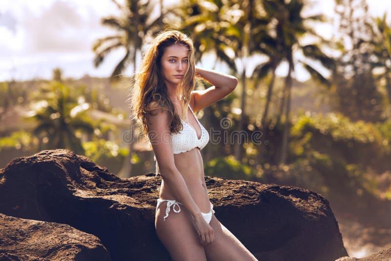 Beautiful young woman in white bikini swimwear posing on tropical beach rocks. royalty free stock photo