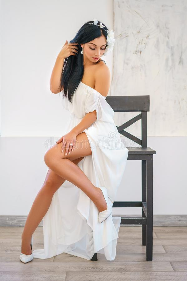 Beautiful young woman in white dress sitting posing on chair royalty free stock photos