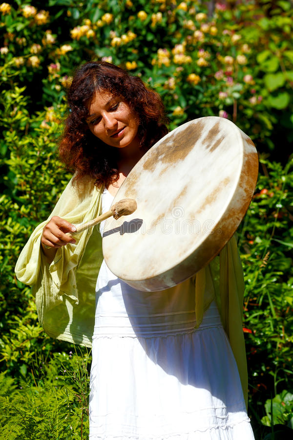 Beautiful shamanic girl with shaman frame drum on background with leaves and flowers. royalty free stock photography