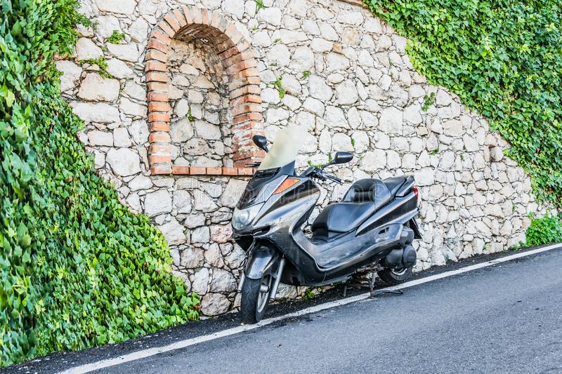A beautiful shiny black motorbike with reflections is on the side of the road by an old gray stone wall with an orange arch and royalty free stock image
