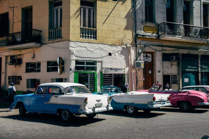 3 beautiful classic cars in Havana, Cuba. 3 beautiful shiny classic cars parked by a restaurant in Havana, Cuba royalty free stock image