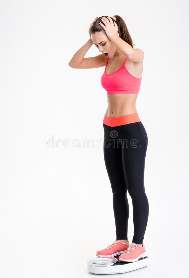 Beautiful shocked young sportswoman standing on weighing scale. Full length of beautiful shocked young sportswoman standing on weighing scale over white stock images