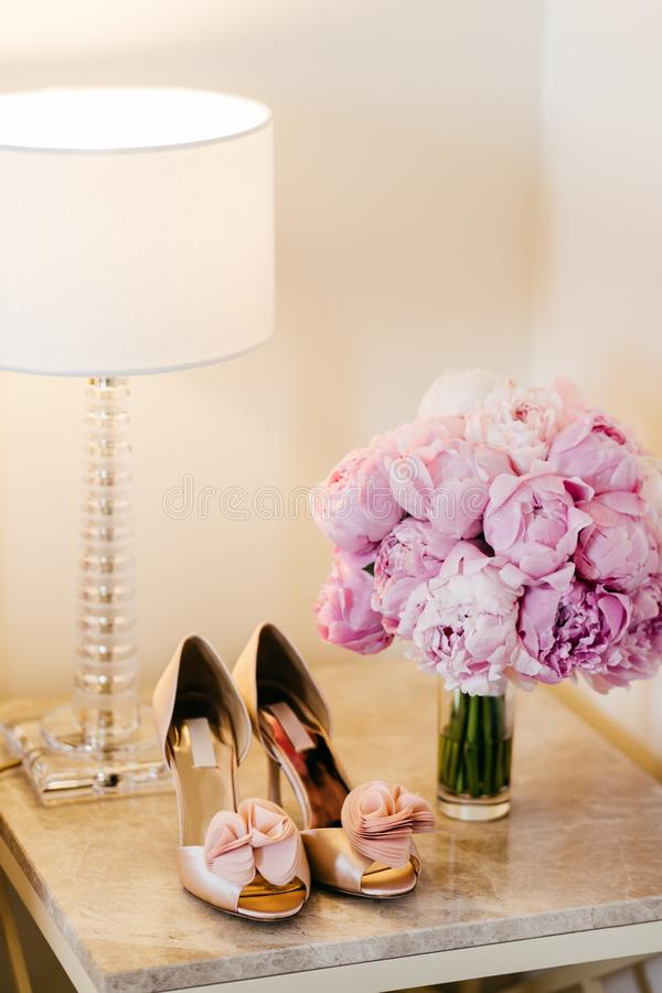 Beautiful shoes with high heels, lamp and bouquet with pink flowers standing on bedside-table. Bouquet and shoes of bride. Wedding stock photography