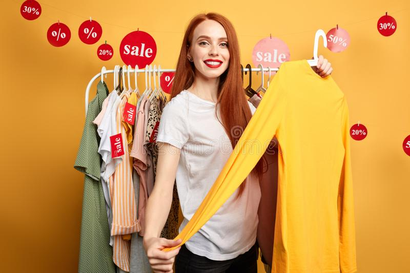 Beautiful shop assistant offers clothes to customers royalty free stock photos