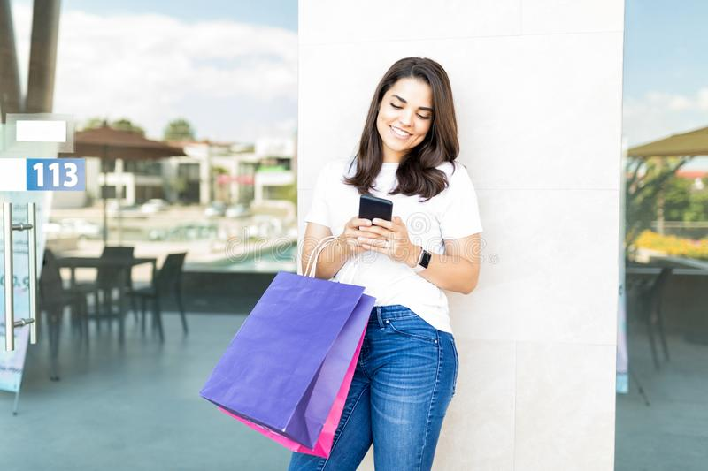 Beautiful Shopper Smiling While Using Smartphone In Shopping Center stock image