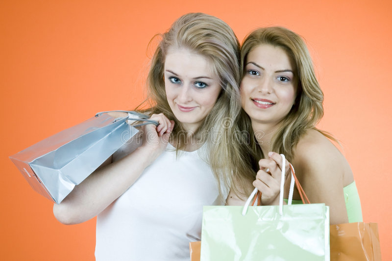 Beautiful Shoppers. Portrait of two woman holding multiple shopping bags. Taken in studio with orange background royalty free stock photos