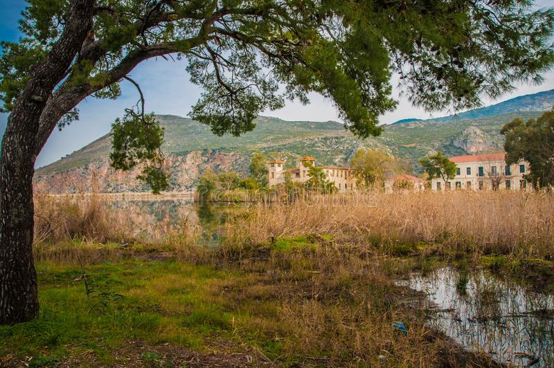 Beautiful shores of Kaifa lake and old ruined buildings and their reflections in water on Peloponnese in Greece. Image of beautiful shores of Kaifa lake and old royalty free stock photo