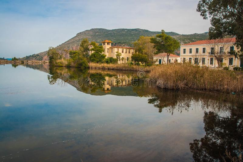Beautiful shores of Kaifa lake and old ruined buildings and their reflections in water on Peloponnese in Greece. Image of beautiful shores of Kaifa lake and old royalty free stock image