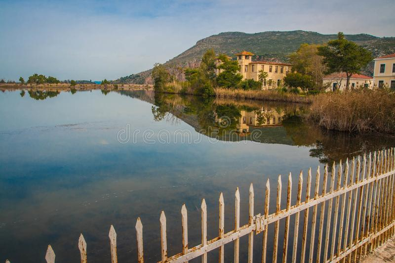 Beautiful shores of Kaifa lake and old ruined buildings and their reflections in water on Peloponnese in Greece. Image of beautiful shores of Kaifa lake and old royalty free stock photography
