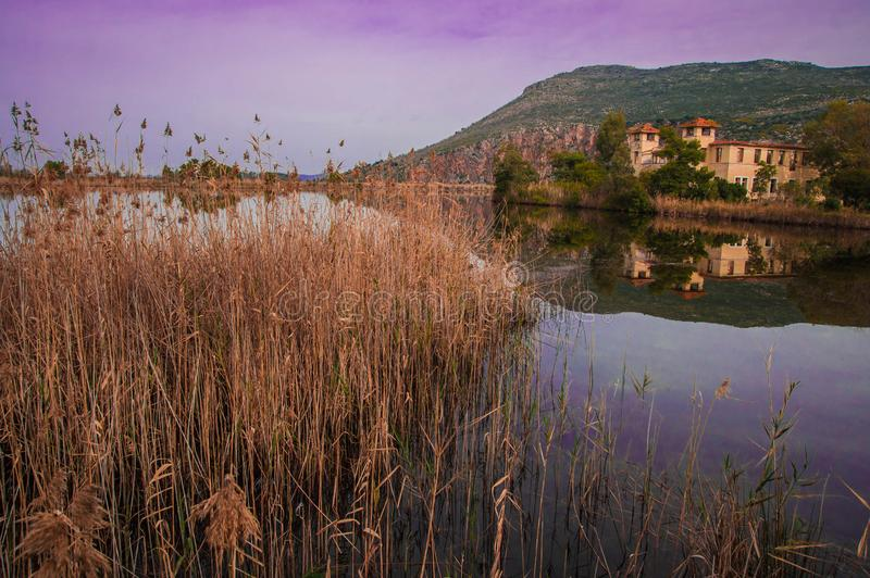 Beautiful shores of Kaifa lake and old ruined buildings and their reflections in water on Peloponnese in Greece. Image of beautiful shores of Kaifa lake and old stock photography