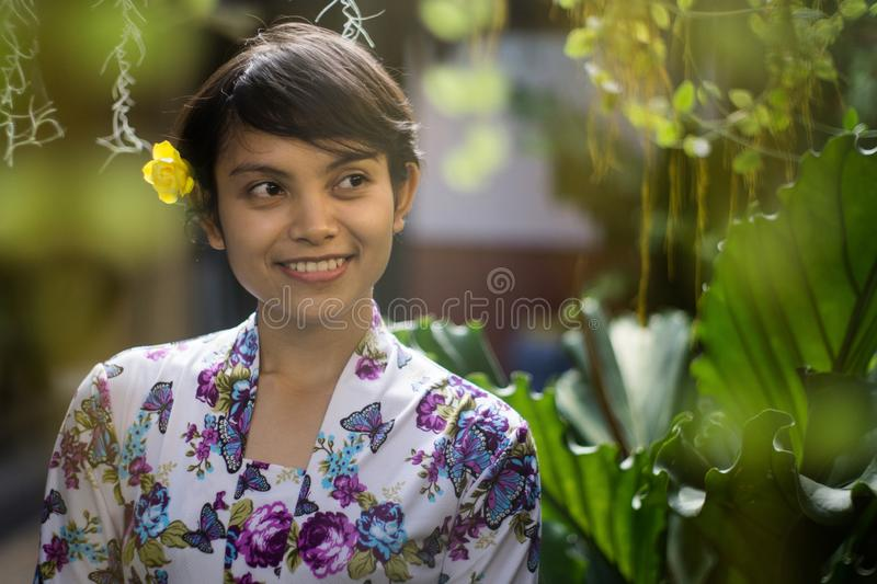 Beautiful short hair Asian Indonesian girl smelling with nature green background. She using floral pattern traditional shirt and a royalty free stock photos