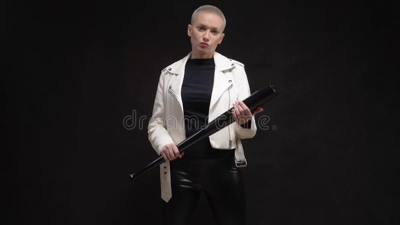 Beautiful  short haired woman in a white leather jacket with a baseball bat royalty free stock images