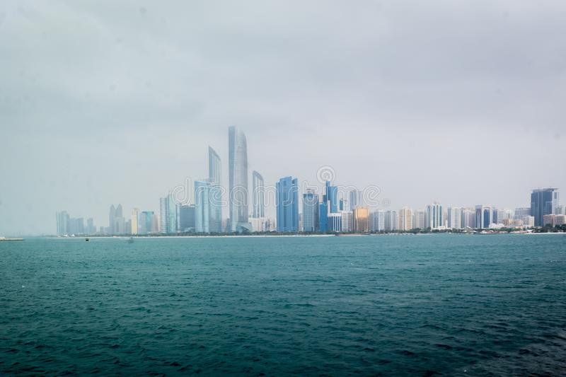 Beautiful shot of Abu Dhabi city skyline towers and beach on a cloudy day stock photo