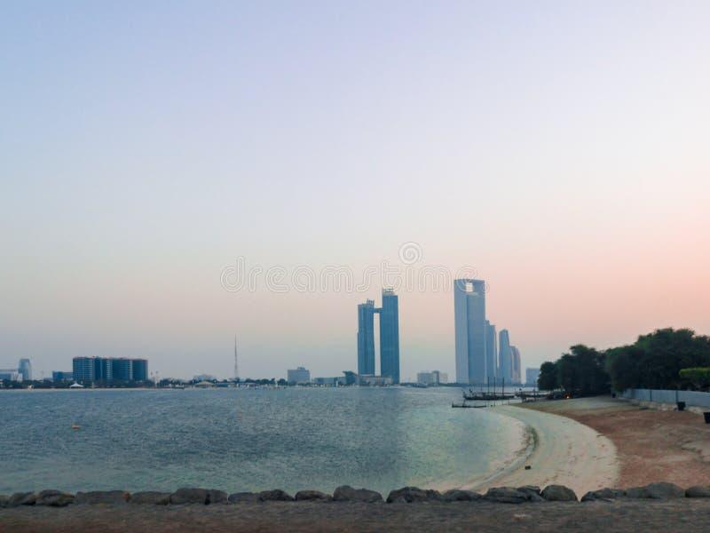 Beautiful shot of Abu Dhabi city towers and beach at sunset stock image