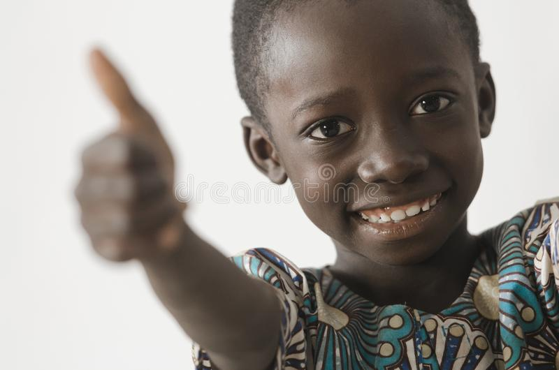 Handsome young African boy showing his thumbs up as a success symbol, isolated on white stock image