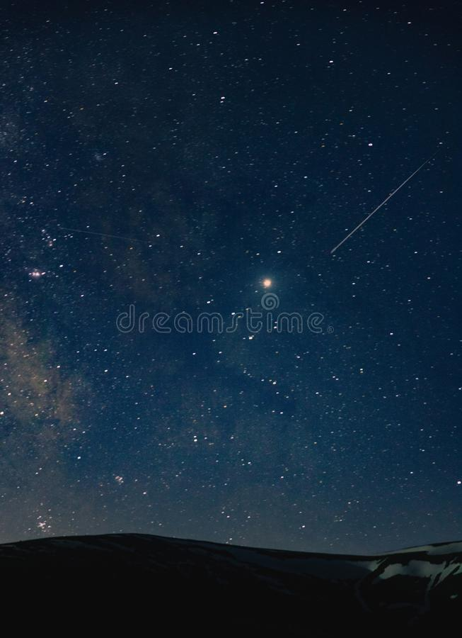 A beautiful shot of an amazing sky full of breathtaking stars at night over the hills stock photos