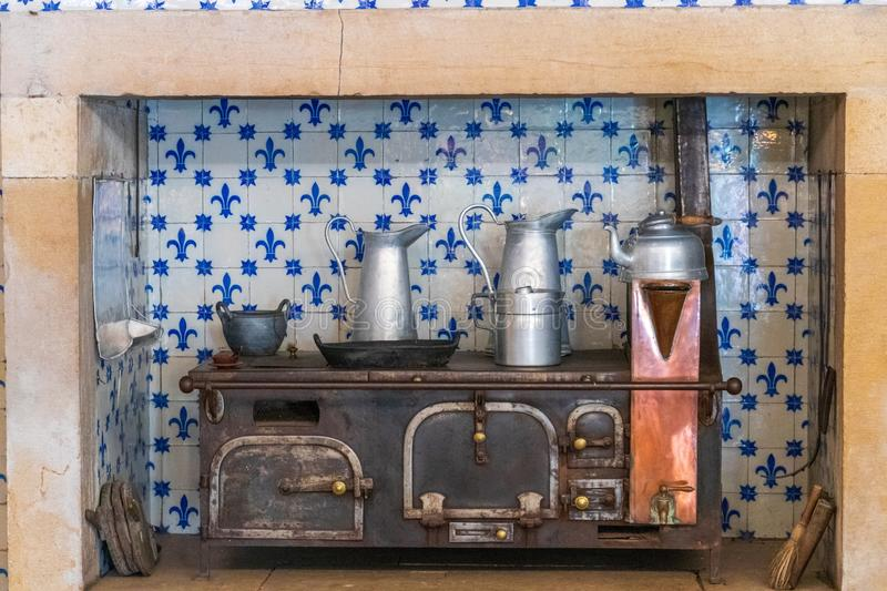 Beautiful shot of antique tableware on iron over in front of a white tile wall with blue patterns royalty free stock photography