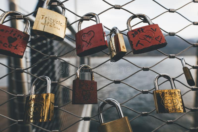 Beautiful shot of assorted-color padlocks on a fence during daytime with a blurry background stock photos
