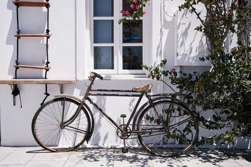 Beautiful shot of a bicycle parked under the window of a white building in Santorini, Greece royalty free stock photos