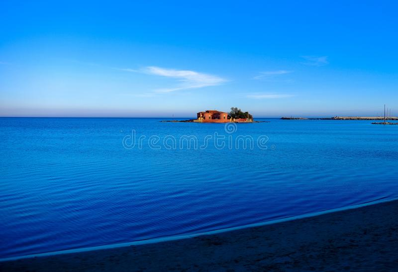 Beautiful shot of a big house in the middle of the sea under a blue sky. A beautiful shot of a big house in the middle of the sea under a blue sky stock photography