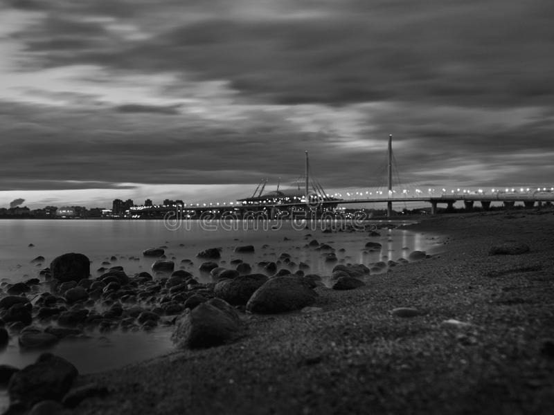 Beautiful shot of the bridge over the water under a cloudy sky in black and white. A beautiful shot of the bridge over the water under a cloudy sky in black and stock photo