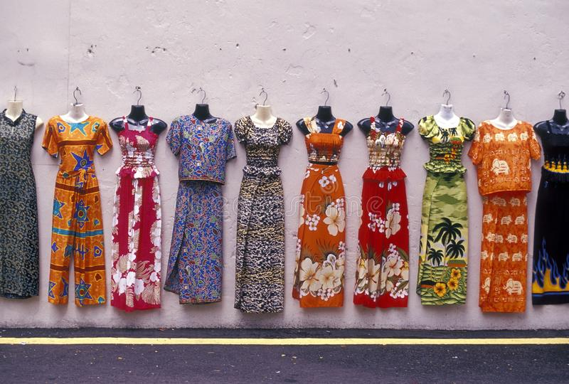 Beautiful shot of different dresses hanging from a stand with a white surface in the background. A beautiful shot of different dresses hanging from a stand with royalty free stock photo