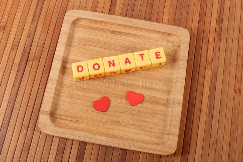 Donate. Beautiful shot of donate spelled on wooden background royalty free stock image
