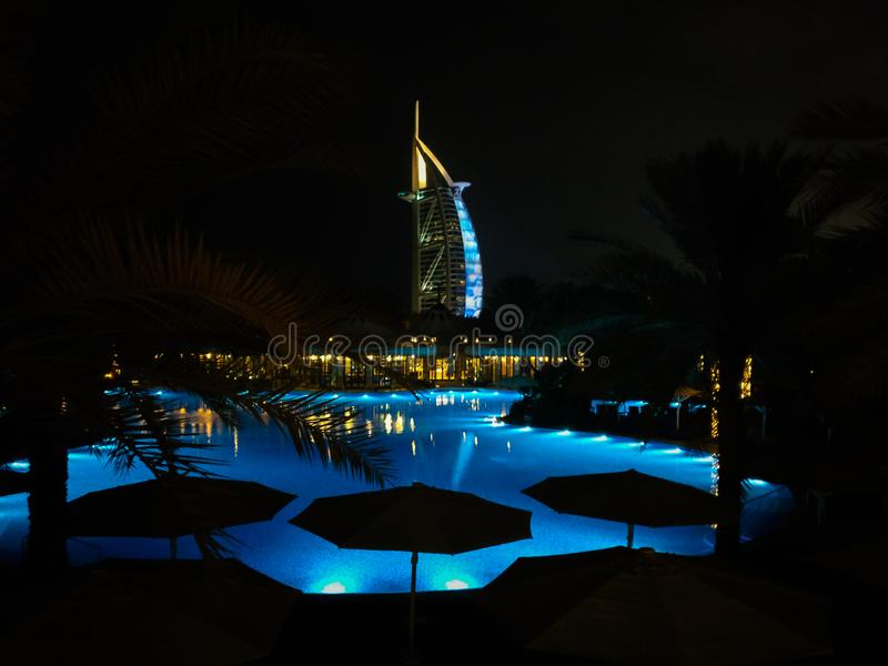 Beautiful shot of Dubai Bur Al Arab landmark at night behind a pool in Jumeirah city royalty free stock photos