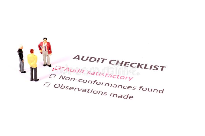 Audit checklist. Beautiful shot of figurines standing on audit checklist royalty free stock photography