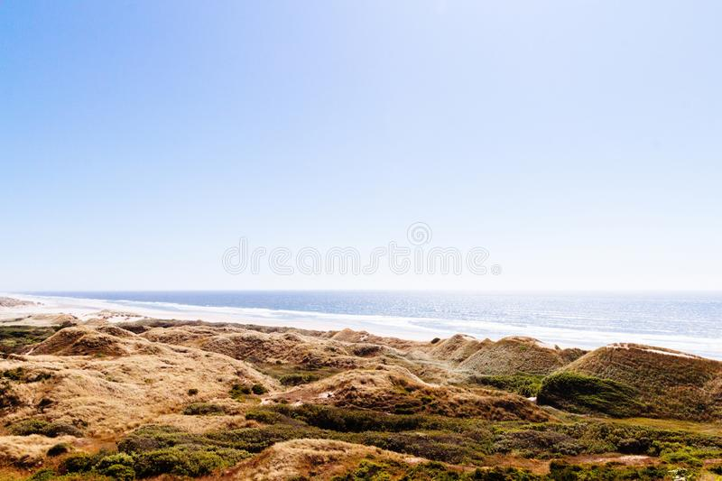 Beautiful shot of green and brown hills near the sea with a blue sky in the background at daytime. A beautiful shot of green and brown hills near the sea with a royalty free stock photo
