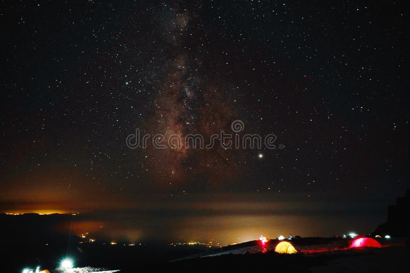 Beautiful shot of illuminated tents in a field under breathtaking sky full of stars royalty free stock images