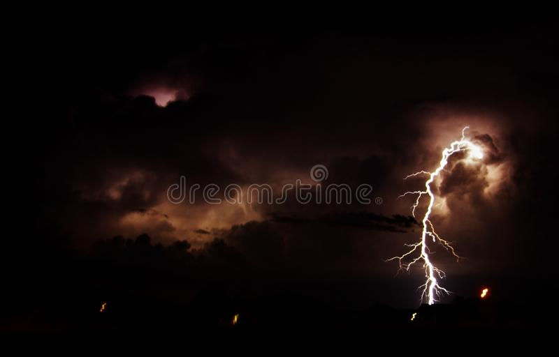 Beautiful shot of a lightning strike in the cloudy night sky royalty free stock photography