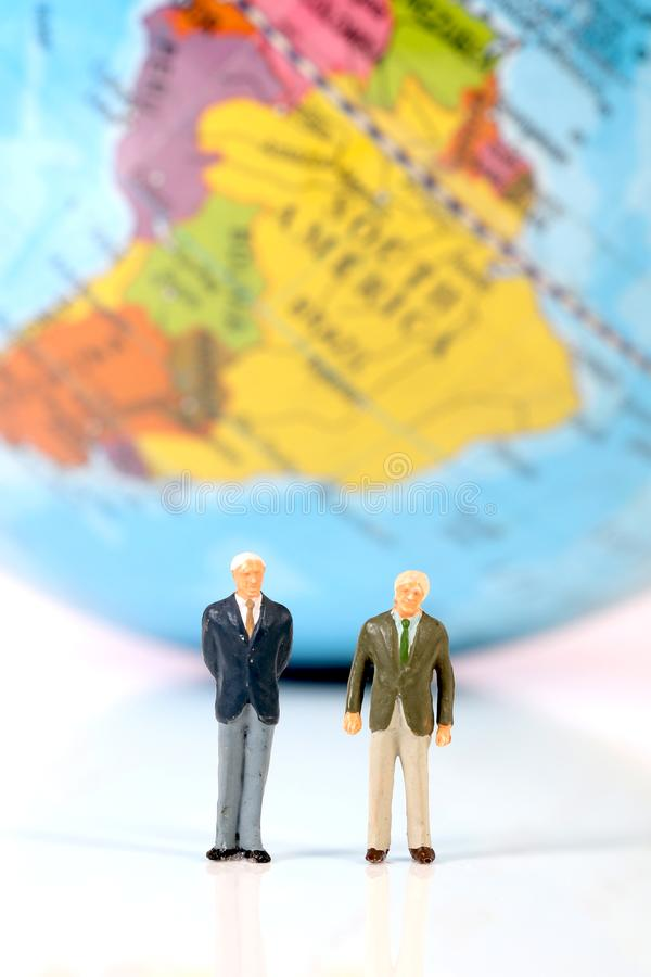 Travel agents. Beautiful shot of male figurines as travel agents standing in front of globe royalty free stock photos