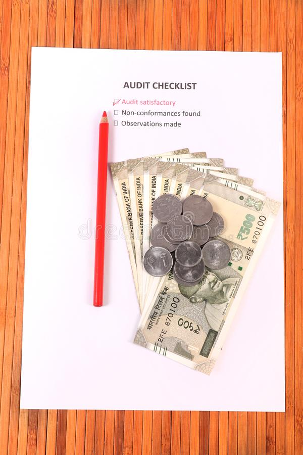 Audit checklist. Beautiful shot of money on audit checklist royalty free stock photo