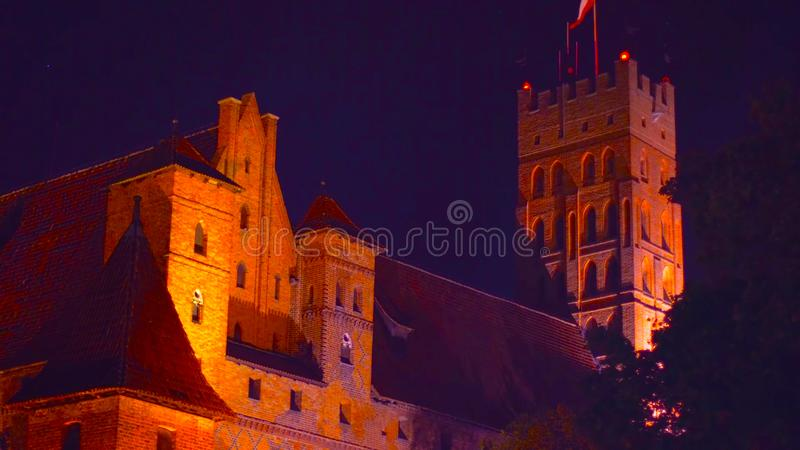 A beautiful shot next to an old castle at night with a glowing light _ in a traditional place _ in the pogrom of Poland 1-2019.  royalty free stock image